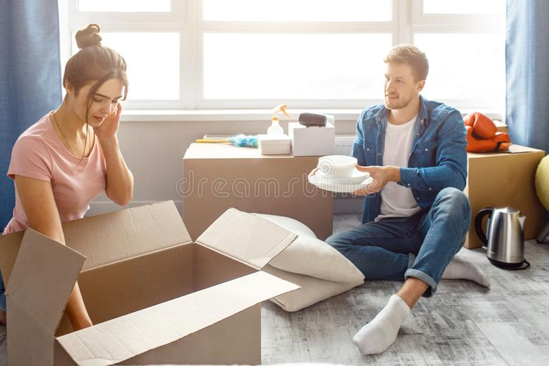 Young family couple bought or rented their first small apartment. Guy sit on floor and hold white plates. Young woman stock images