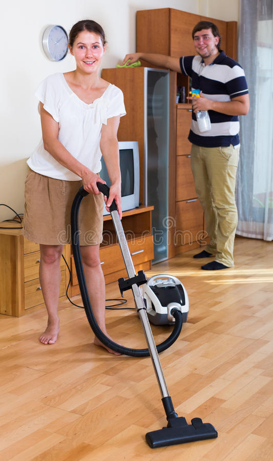 Young family couple doing regular clean-up. At home and smiling royalty free stock photos