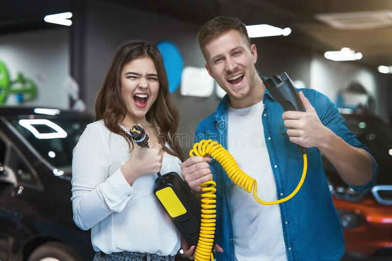Young family couple handsome man and beautiful brunette woman holding charging cable for electric car , looking excited stock photo