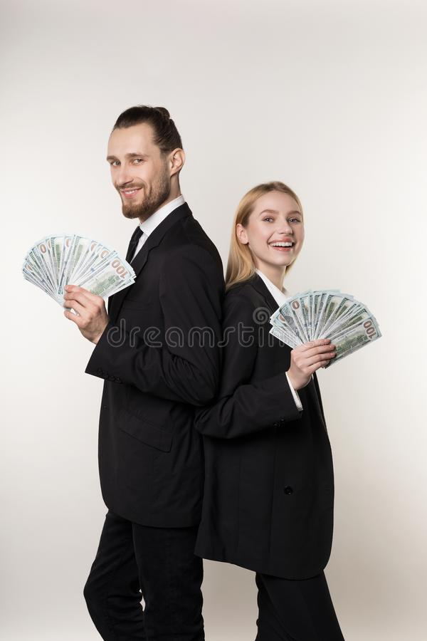 Young family couple handsome man and his beautiful blonde wife, both in black suits standing back to back with money in royalty free stock photos