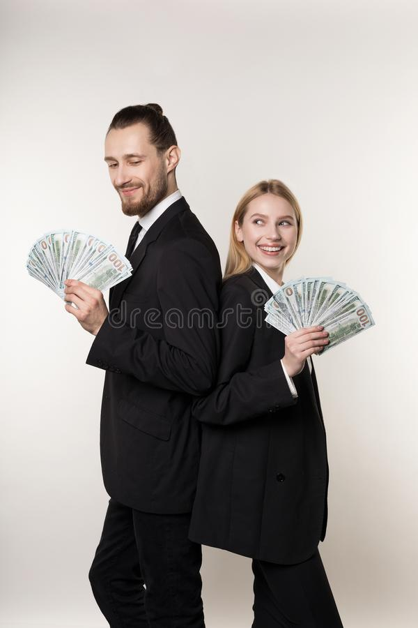 Young family couple handsome man and his beautiful blonde wife, both in black suits standing back to back with money in royalty free stock image