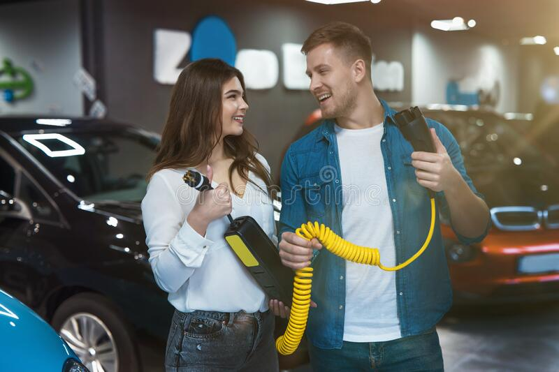 Young family couple handsome man and beautiful brunette woman holding charging cable for electric car , smiling to each other, royalty free stock photos