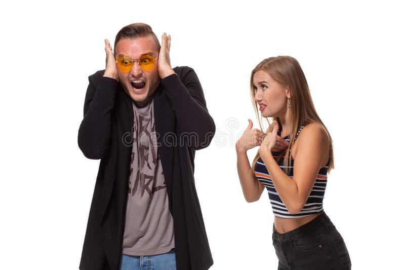 Angry blonde young European woman gestures with hands, shouts at husband who is guilty, stands together against white. Young family couple have conflict. Angry royalty free stock image