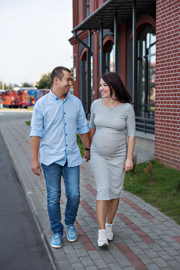 Family couple men and a young pregnant woman walking holding hands and laughing along the city windows stock photo