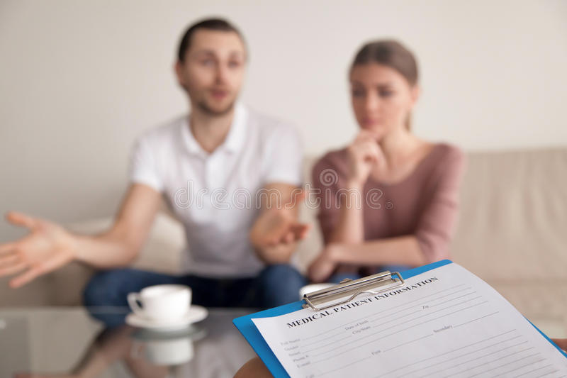 Young family couple at the psychologist discussing problems in m. Unhappy men telling family psychologist his opinion about problems in marriage while his royalty free stock photos
