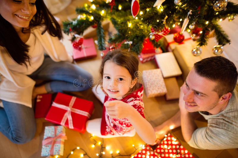 Young family with daugter at Christmas tree at home. royalty free stock photos