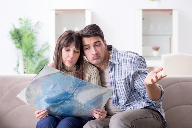 The young family discussing travel plans with map. Young family discussing travel plans with map stock images