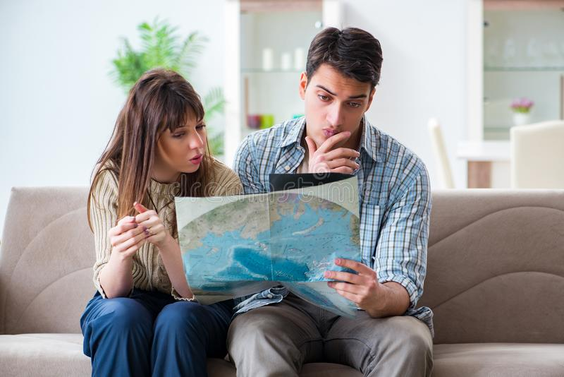 The young family discussing travel plans with map. Young family discussing travel plans with map stock photo