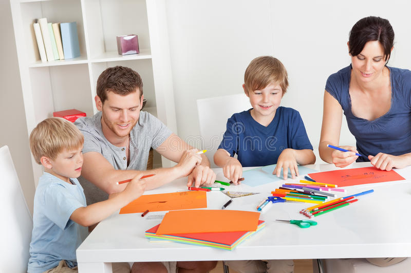 Young family drawing with colorful pencils. Young family drawing together with colorful pencils at home royalty free stock photos