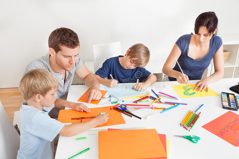 Young family drawing with colorful pencils. Young family drawing together with colorful pencils at home royalty free stock photo