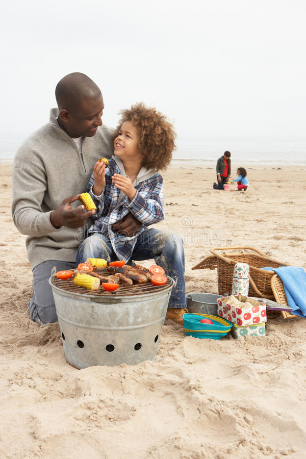 Young Family Enjoying Barbeque On Beach stock photos