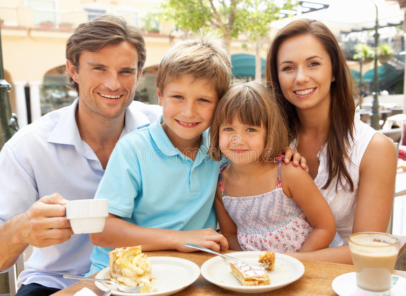 Young Family Enjoying Cup Of Coffee And Cake. In Cafe Together royalty free stock photo
