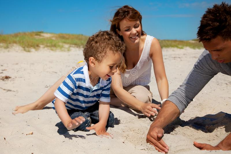 Young Family Enjoying Summer On A Beach Stock Photo