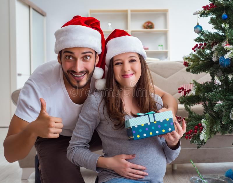 Young family expecting child baby celebrating christmas. The young family expecting child baby celebrating christmas stock photos