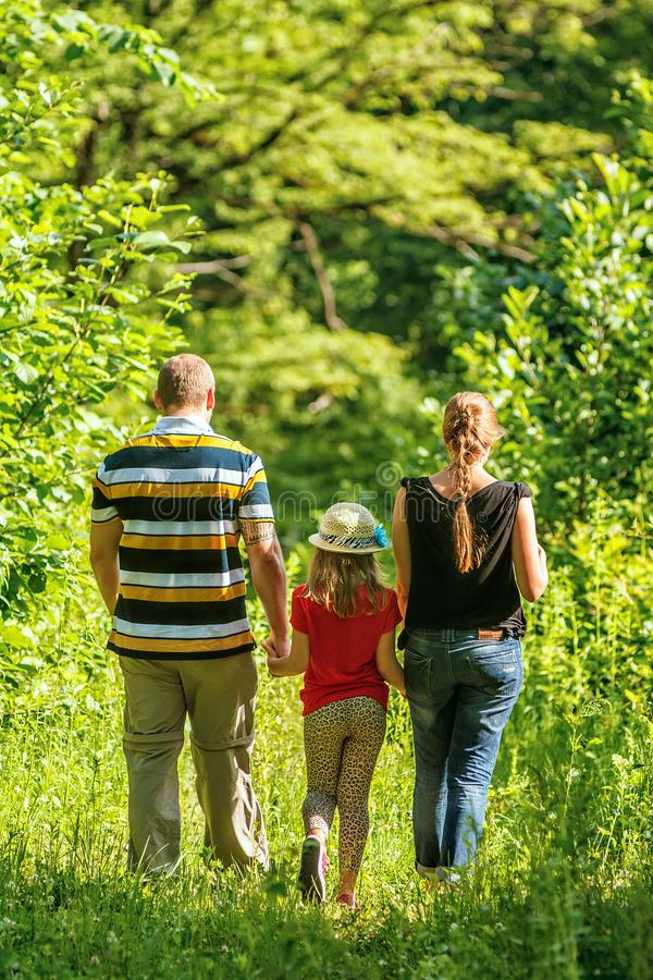 Young family of father, mother and daughter walks together in sunny summer mountain forest holding each others` hands stock photo