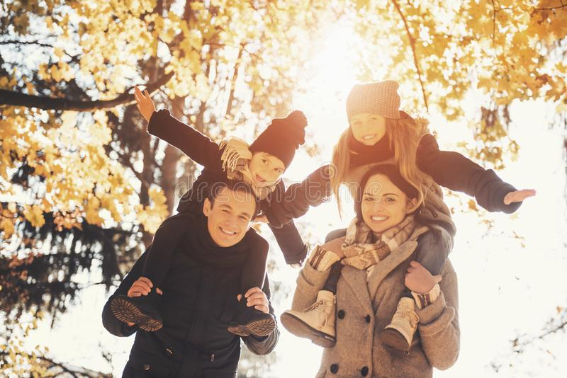 Young Family of Four Have Fun in Autumn Park. royalty free stock photography