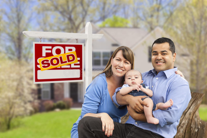 Young Family in Front of Sold Real Estate Sign and House. Happy Mixed Race Young Family in Front of Sold Home For Sale Real Estate Sign and House royalty free stock photo