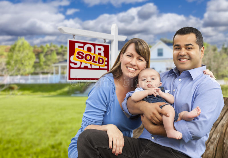 Young Family in Front of Sold Real Estate Sign and House. Happy Mixed Race Young Family in Front of Sold Home For Sale Real Estate Sign and House stock photos