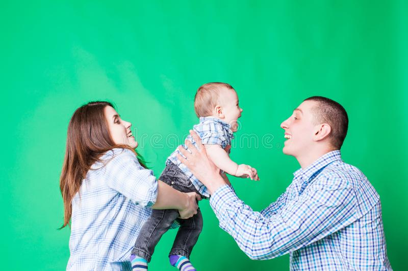 Young family fun over the green wall royalty free stock photos