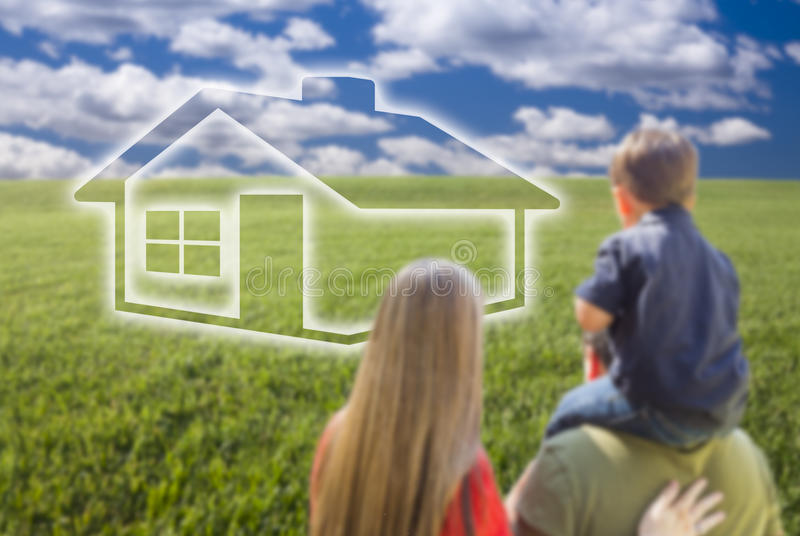 Young Family in Grass Field with Ghosted House in Front. Of Them royalty free stock images