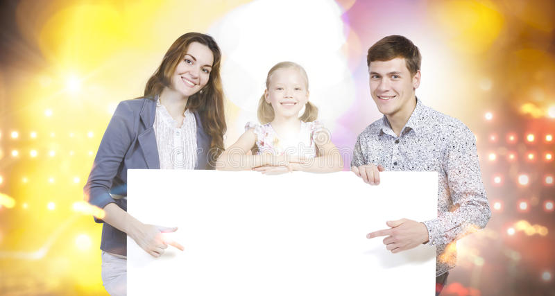 Young family. Happy family of three holding white blank banner. Place for text stock image