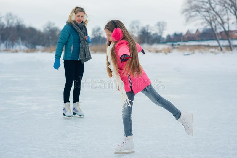 Young family have fun on the ice area in a snowy park royalty free stock photography