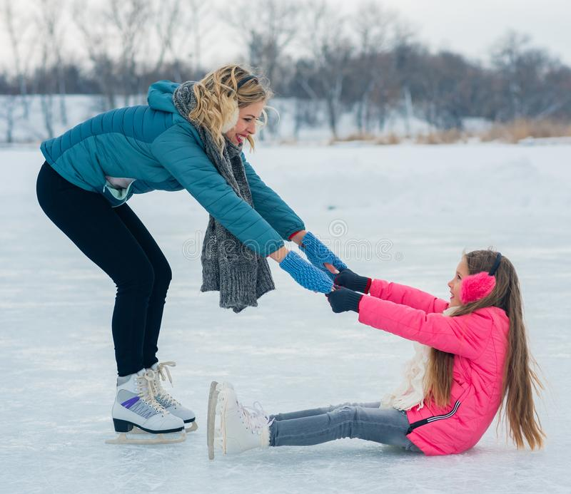 Young family have fun on the ice area in a snowy park stock photo