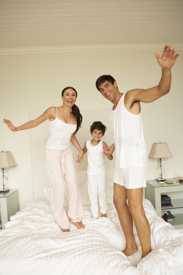 Young Family Having Fun Bouncing On Bed stock images