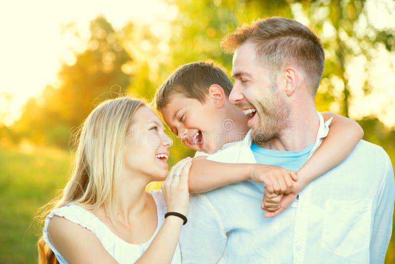 Young family having fun outdoors. Happy joyful young family having fun outdoors stock photo