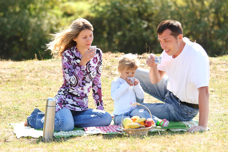 Young family having a picnic in nature royalty free stock image