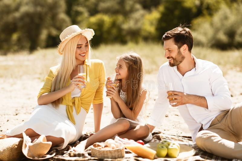 Young family having picnic outdoors, resting in nature. And drinking orange juice stock photography