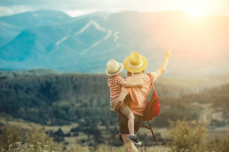 Family traveling in Rila mountains Bulgaria. Young family hiking in Rila mountains, Bulgaria. A child in the arms of a woman. back view. mom pointing at the royalty free stock image