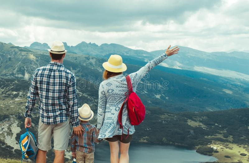 Family traveling in Rila mountains Bulgaria. Young family hiking in Rila mountains, Bulgaria. the women is holding her hand up. the family is standing on the royalty free stock photo