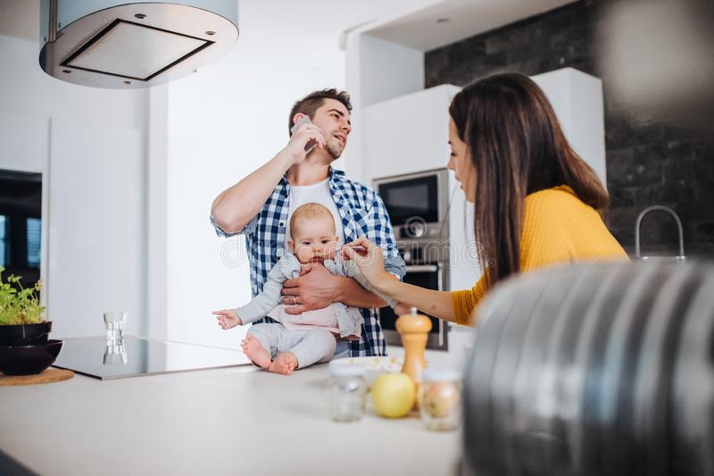 A young family at home, a man holding a baby and a woman feeding her. A portrait of young family standing in a kitchen at home, a men with smartphone holding a royalty free stock images