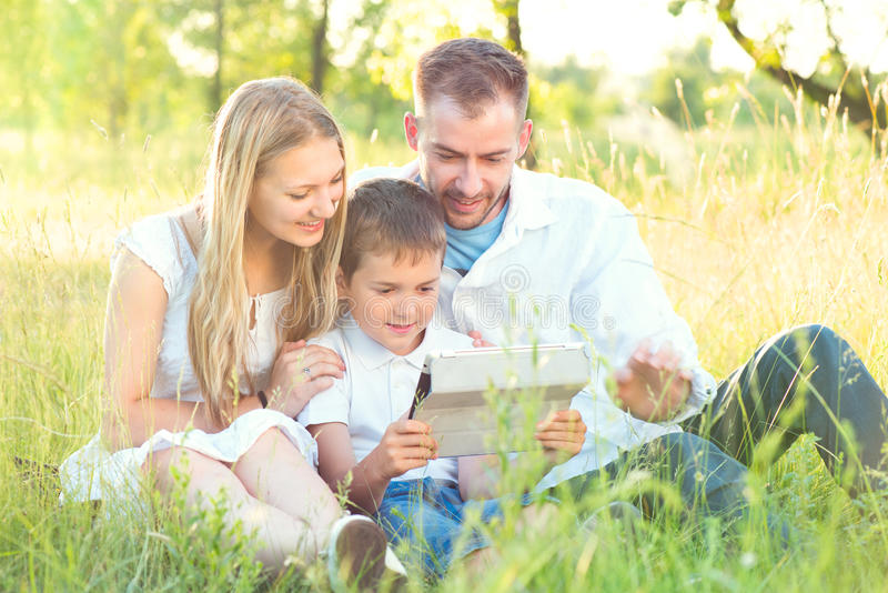 Young family with kid using tablet PC in summer park. Happy young family with kid using tablet PC in summer park royalty free stock photography
