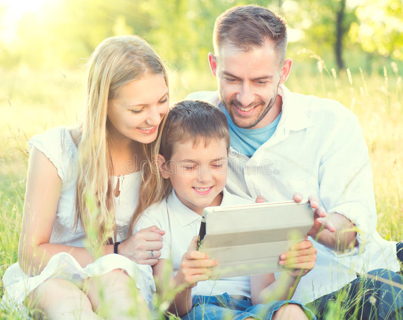 Young family with kid using tablet PC in summer park. Happy young family with kid using tablet PC in summer park royalty free stock images