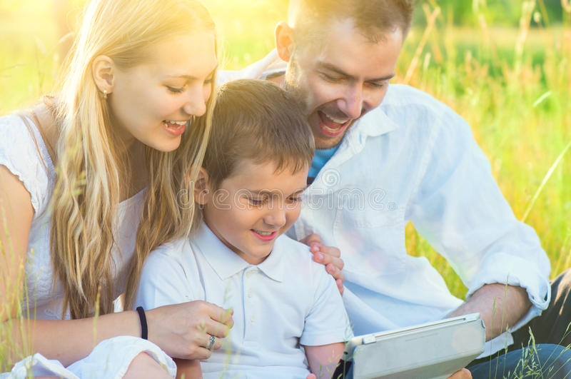 Young family with kid using tablet pc in summer park. Happy young family with kid using tablet pc in summer park royalty free stock photos