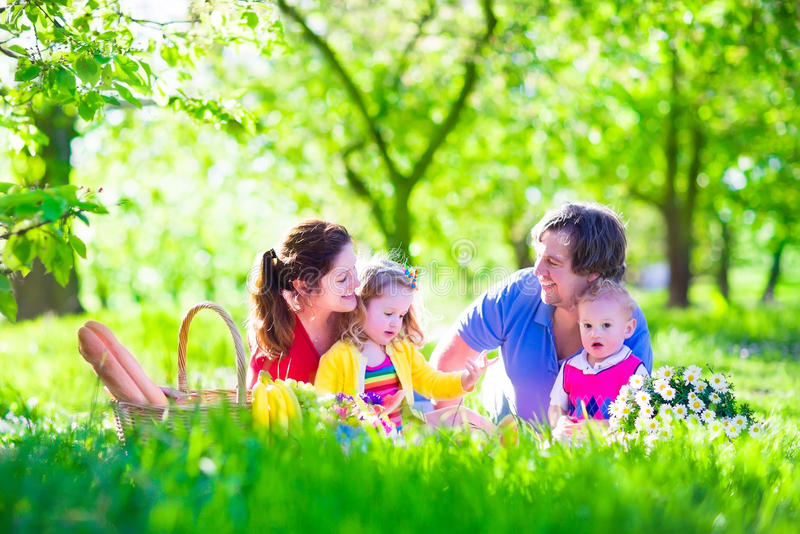 Young family with kids having picnic outdoors. Parents with two children relax in a sunny summer garden. Mother, father, little girl and baby boy eat sandwich stock photo