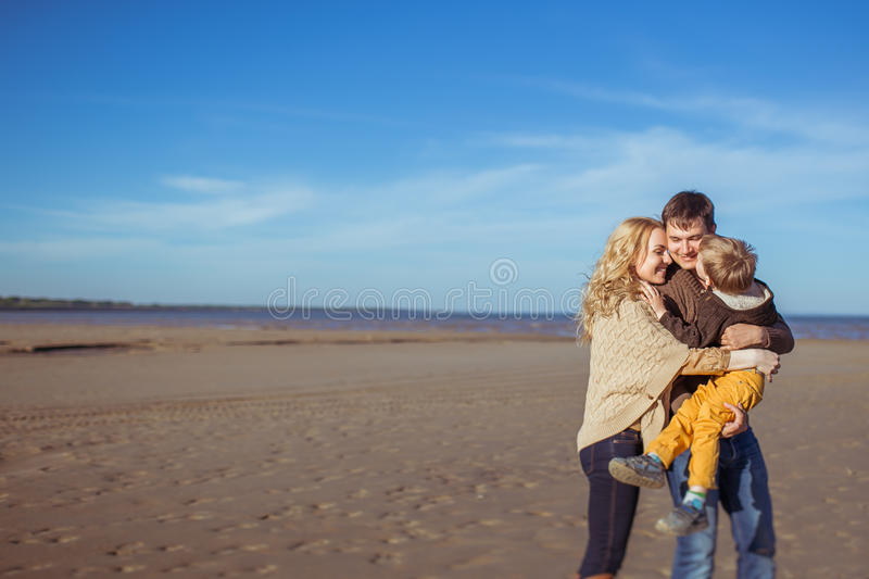 A young family kissing and embracing at the beach stock image