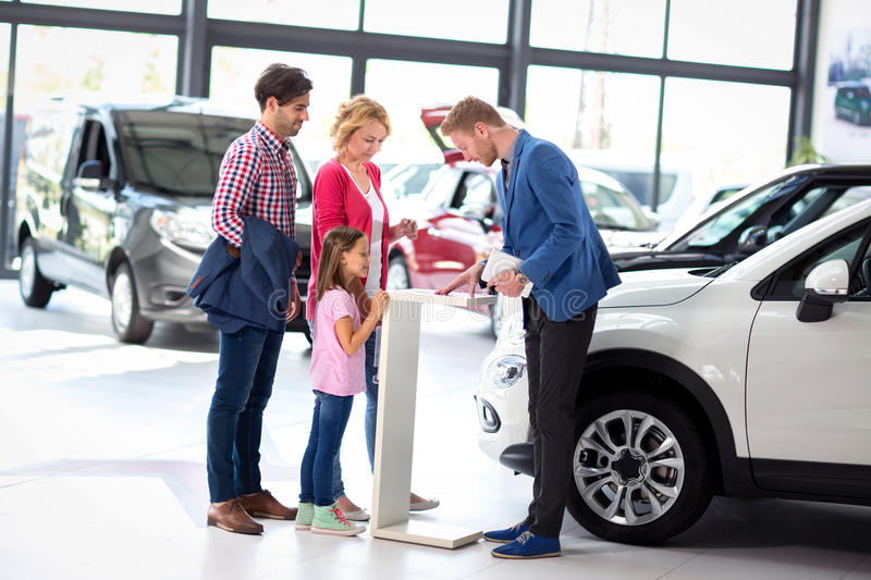 Young family listens carefully car dealers. While their polite salesman presents an offer royalty free stock images