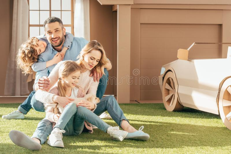 young family with little labrador puppy on yard of royalty free stock images
