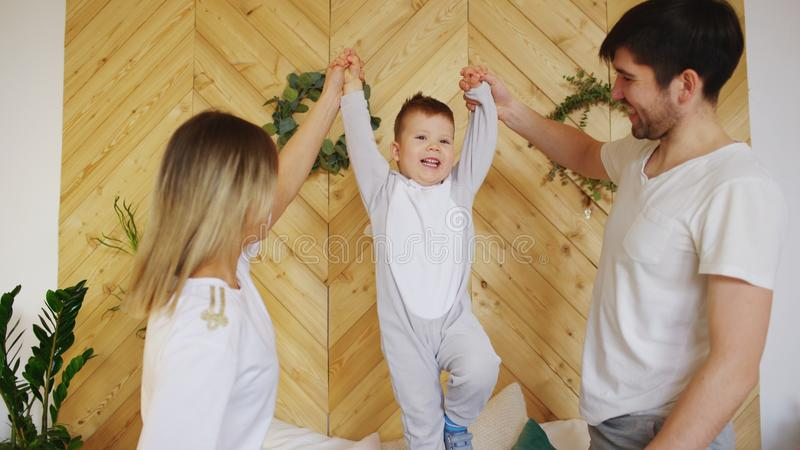A young family with little son play on bed in the bedroom royalty free stock photos