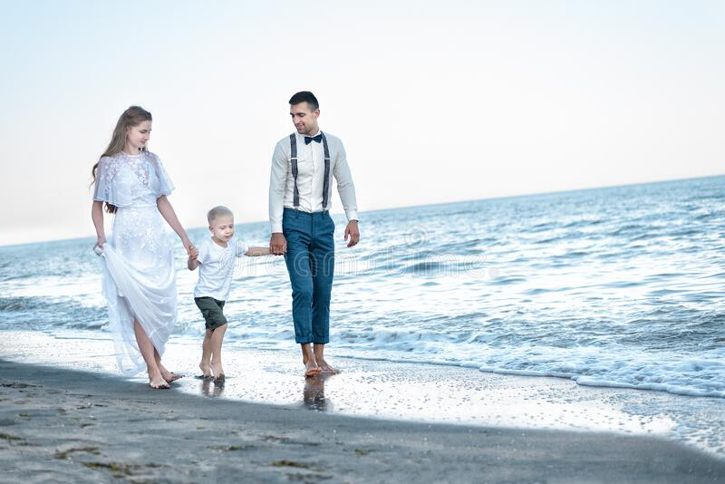 Young family with little son walk on the beach of ocean Walking along the sea shore.  stock photography