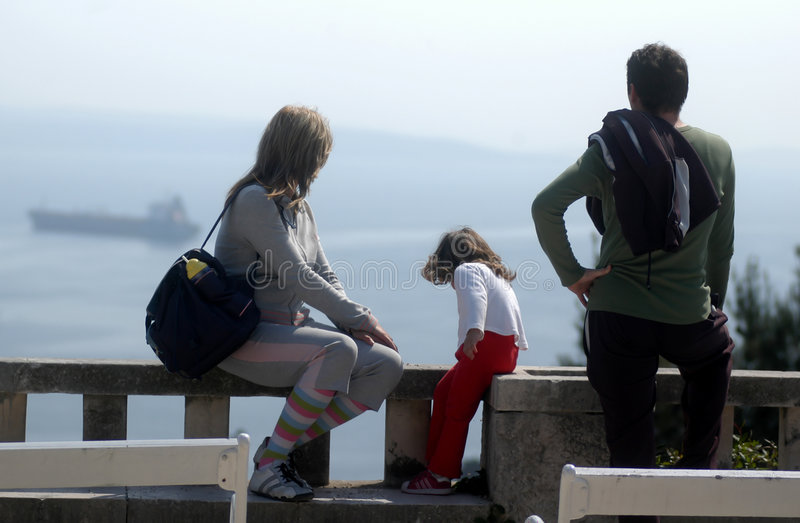 Young family at the lookout. Happy family watching big boat on the sea stock image