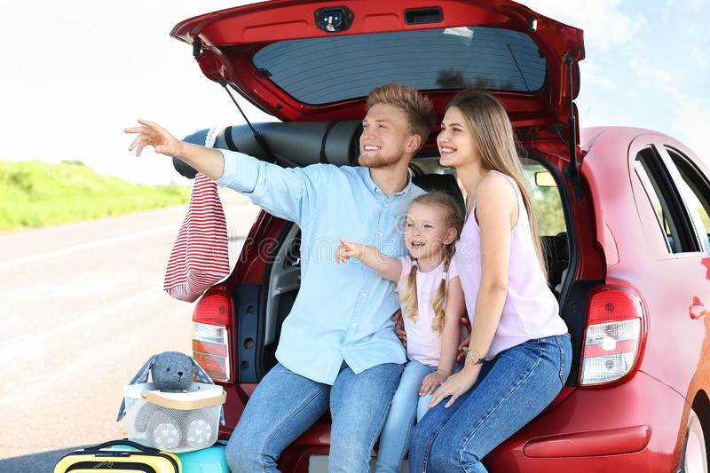 Young family with luggage near car trunk royalty free stock image