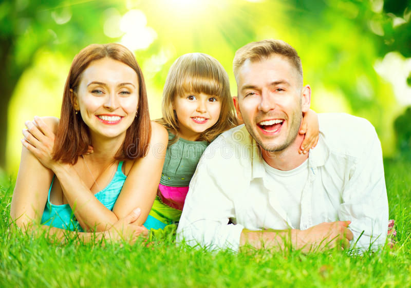 Young family lying on green grass. Happy joyful young family lying on green grass royalty free stock image