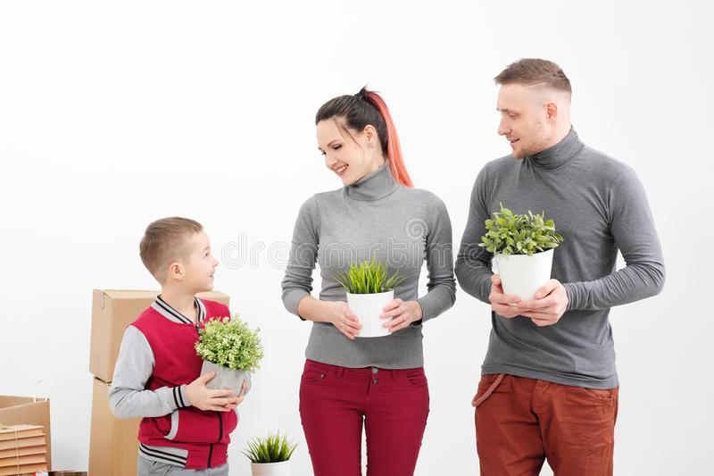 Young family, man woman and child son in new apartments. They are holding green potted plants. Boxes with cargo on a stock image