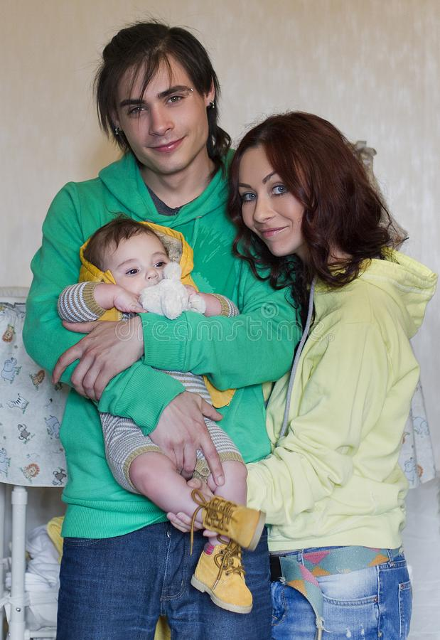 Young family mom, dad and son at home. Happy couple holding a baby, they hug. young neformal family with facial piercing. mom, dad and son at home stock photos
