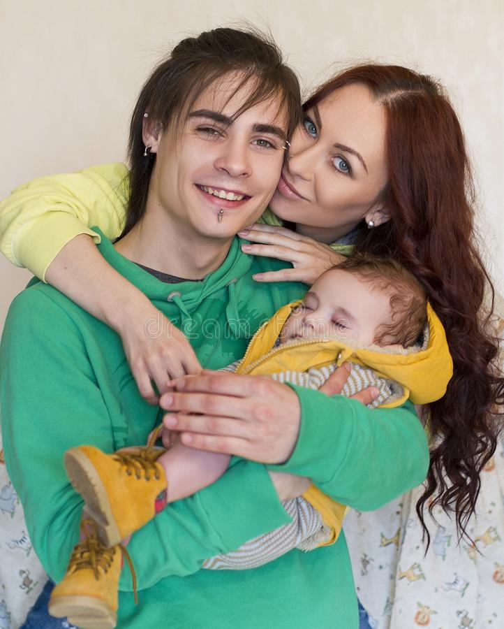 Young family mom, dad and son at home. Happy couple holding a baby, they hug tenderly. young neformal family with facial piercing. mom, dad and sleeping son at royalty free stock image