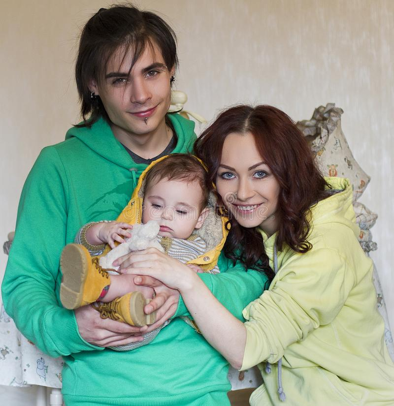 Young family mom, dad and son at home. Happy couple holding a baby. young neformal family with facial piercing. mom, dad and son at home stock photo